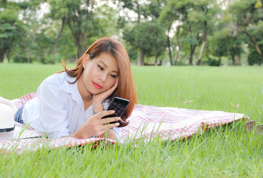 Asian women happy while picnic in the garden,Asian women  enjoy using smartphone while picnic,Asian women happy with Social network in the garden