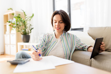 business, savings, finances and people concept - woman with tablet pc, papers and calculator at home