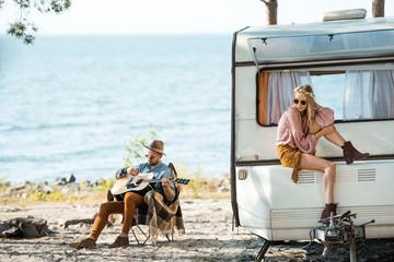 beautiful hippie girl sitting on campervan while man playing guitar near sea