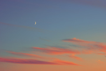 sunset half moon pink clouds.