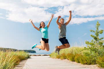 fitness, sport and lifestyle concept - happy couple in sports clothes jumping on beach