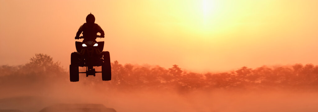 Silhouette ATV or Quad bikes Jump in sunset.