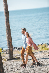 beautiful hippie couple holding hands and walking in nature near sea
