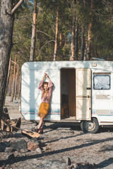 attractive hippie girl posing near campervan in forest