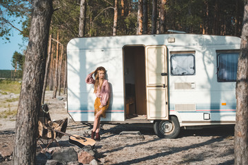 beautiful hippie girl posing near camper van in forest