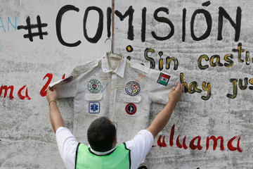 Man places the shirt of a rescue worker at the site where a building collapsed during the September 2017 earthquake in Mexico City