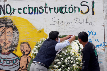 Man arranges a wreath to honour the victims of a building that collapsed during the September 2017 earthquake in Mexico City
