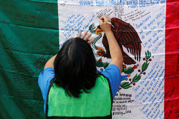 Woman writes a message on Mexico's flag before a homage to the victims of a building that collapsed during the September 2017 earthquake in Mexico City