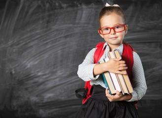 Cute little schoolgirl in glasses on blackboard