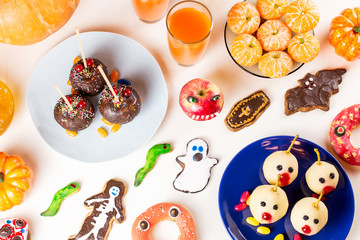 Halloween sweet treats, party food concept. Scary cookies, monster biscuits and fruits on grey background.