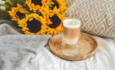 Cup with cappuccino, sunflowers, bedroom, morning concept, autumn time, toned photo