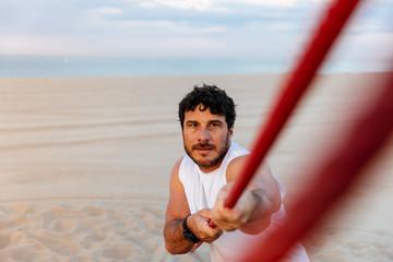 Handsome sportsman pulling rope
