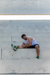 Tired sportsman stretching on steps