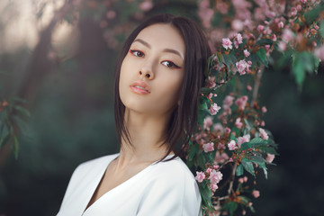 Asian woman fashion close-up portrait. Beautiful mixed race asian caucasian young girl perfect skin creartive art make-up wearing trendy white japanese kimono standing agaist flower background. Spring