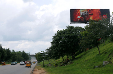 Vehicles drive past a billboard advertising Coca-Cola in Abuja