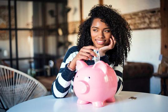 Black woman with saving piggy bank