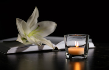 Burning candle, book and white lily on table in darkness, space for text. Funeral symbol
