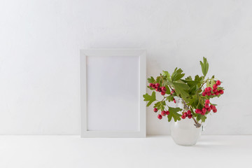 Mockup white frame and branches with red berries in a vase