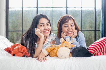 Happy teenage girls friend using mobile phone for online shopping in bedroom