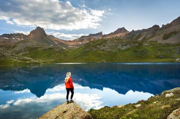 Woman on shore of Ice Lake, San Juan mountains, Silverton, Colorado, USA