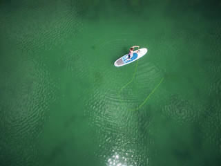 Aerial view of young man fishing from his paddle board on high alpine lake in Colorado, USA