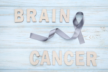 Grey ribbon on wooden table. Brain cancer concept