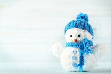 Small snowman toy on wooden table
