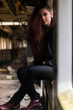 portrait Young woman with long grounge red hair posing in an abandoned train window
