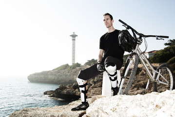 Portrait of mountain biker on coastline