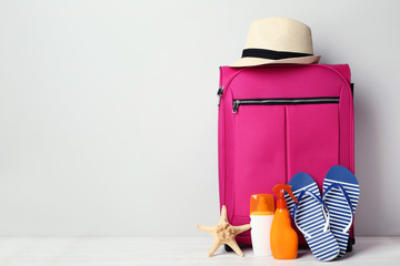 Pink suitcase with flip-flops, hat and sunscreen bottles on wooden table