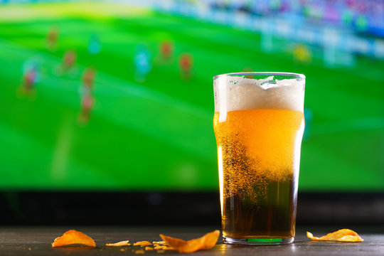 A glass of beer on a dark wooden table with crushed potato chips. Football on a background, high resolution