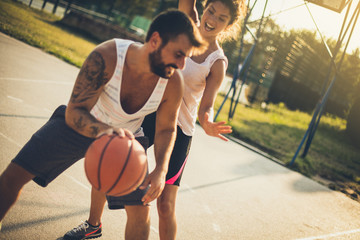 Young couple playing basketball. Moving activity.