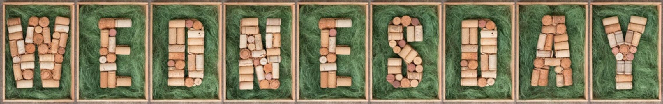 Word Wednesday made of wine corks on green background in wooden box