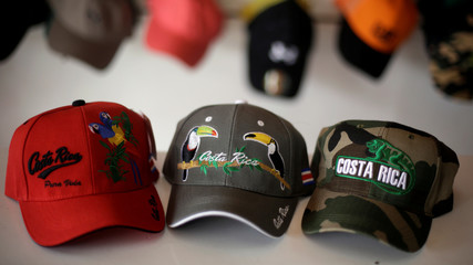 Hats with drawings of animals emblematic of Costa Rica are displayed at the World of Caps shop in Heredia