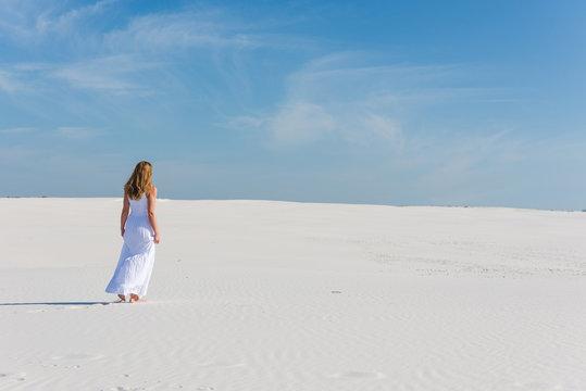 Woman in white long dress walk in desert