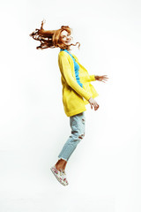 pretty young redhad teenage girl  jumping happy smiling on white