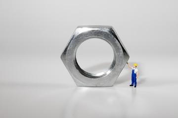 Ingenieurwesen Maschinenbau Handwerkerin Blaumann und Helm  Figur steht vor einer Schraubenmutter
