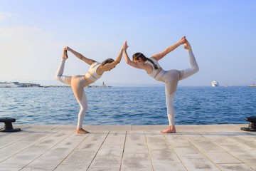 Two matching girls doing yoga dancer pose by water