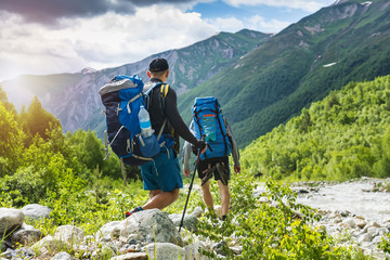 Trekking in mountains. Mountain hiking. Tourists with backpacks hike on rocky way near river. Wild nature with beautiful views. Sport tourism in Svaneti, Georgia. Hikers and climbers in mounts. Wall mural