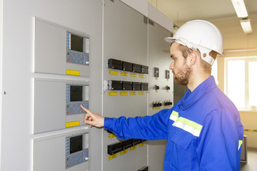 Electrician Engineer on control board. Worker controls industrial processes. Automation point for control machines. High tech in energy
