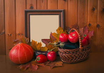 Fresh vegetables, autumn leaves and picture frame