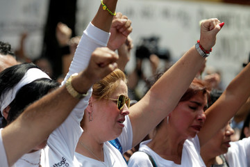 Families of the Tlalpan housing project, affected by the September 2017 earthquake, raise their fist during a minute of silence to honour the victims of the quake in Mexico City