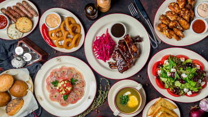 Assorted pork Ribs, tuna carpaccio, chicken wings, Greek salad, onion rings, sausages, sorrel soup top view