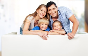 Beautiful smiling family sitting at sofa on background