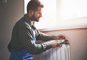 service man with wrench near radiator
