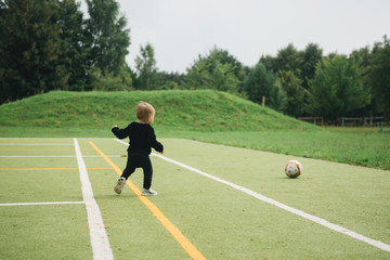 Cute one-year-old kid playing soccer with a ball on artificial grass