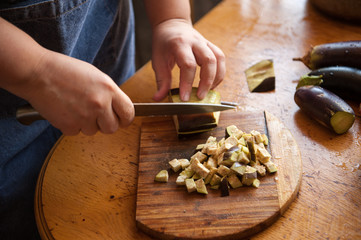 Woman cook in apron and cap cooks in kitchen, cuts eggplants, peppers, onions, garlic on cutting board with large knife. Stir with ladle in saucepan seasoning for canning. Hands close up