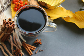A Cup of mulled wine surrounded by yellow autumn leaves and spices, cinnamon sticks, anise, cloves. Warm warming drink, comfort, relaxation, relaxing drink.The view from the top,Copy space. Mulled win