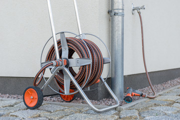 garden hose or water hose with wall of a building in the background