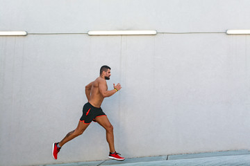 Young muscular male athlete running outdoors